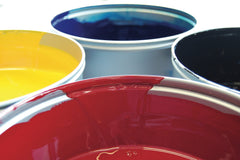 Close up of the tops of paint cans, showing red, yellow, blue and black paint