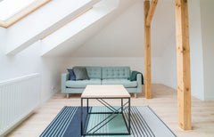 Light blue sofa in a bright open loft area with a slanted ceiling over the sofa.