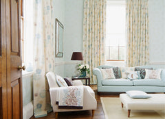 A light blue living room with more traditional looking furniture, curtains that hang from almost the ceiling to floor length.