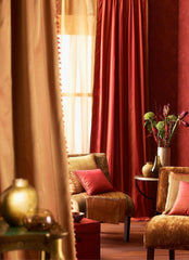 Lush and rich close up of a living room with silk and velvet curtains in beautiful golds and reds.