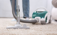 Close up of a vacuum from the floor and a person behind it vacuuming.