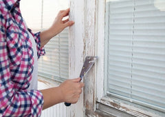 Woman removing trim paint from a window.