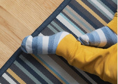 Close up of baby feet in yellow sweatpants and blue and white striped socks.  Baby is sitting on the a striped rug on a light wood floor.
