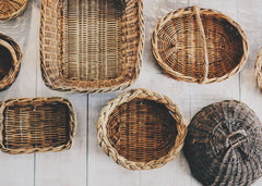 Multiple size and colored baskets hanging on a wall