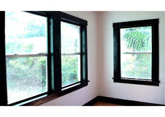 Corner of a room with 3 windows painted with black trim paint