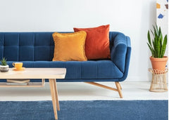 Blue sofa with orange and yellow pillow.