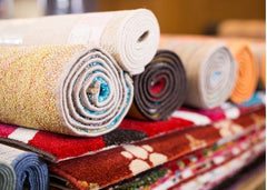 A bunch of rugs stacked up and on top of those are rolled rugs.