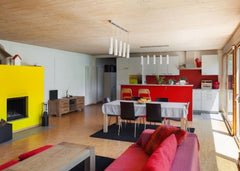 Open living room to dining room and kitchen.  Fireplace is painted bright yellow, sofa is red and there are red accents in the kitchen.