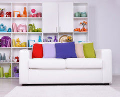 White sofa with multicolored bright accent pillows, bookcase behind sofa with a collection of rainbow items in each square section.