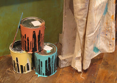 3 paint cans stacked with peach, yellow and blue paint dripping along the sides, next to a drop cloth
