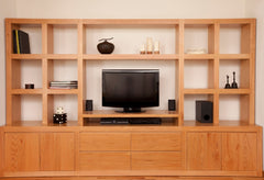 Light wood entertainment center with cabinets below and square shelving above with the television in the center.