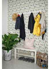 Entry wall with wallpaper, wall hooks with hanging coats, bench below with shoes on it.