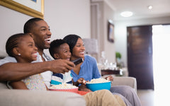 A black family with one boy and one girl child are sitting on the sofa watching television.
