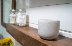Close up angle view of a wood shelf, two jars of cotton balls and q-tips are sitting on the shelf, as well as a clay jar