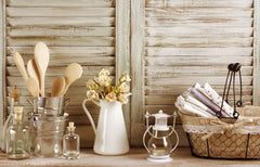 Wooden shutters, and in front are various items like glass jars, black wire basket with napkins and a vase with flowers