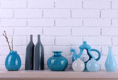 Simple shelf on a white brick wall with different tones of blue items