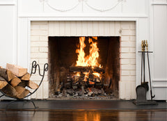 Fireplace with a fire going, a stack of wood on the left side and fireplace tools on the right side.