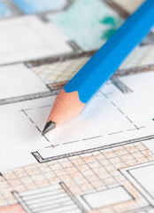 Close up of a colored floor plan with a blue pencil sitting on top.