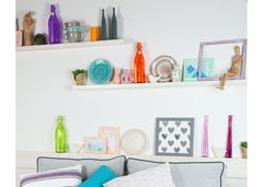Floating shelves above a sofa with fun colored bottles and various items.