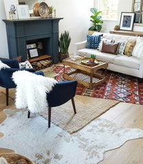 Small living room with a fireplace and 3 rugs are layered