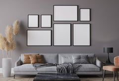 Gray living room wall with a sofa and chair in front, above the sofa are large black framed photos hanging in a gallery style.