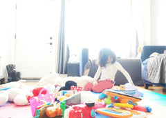 Little girl playing on the floor in a living room surrounded by a lot of toys
