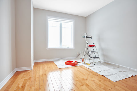 Empty room with wood floors, drop cloth and ladder as if someone is prepping for painting.