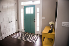 Small foyer area with a teal door, and yellow entry table.