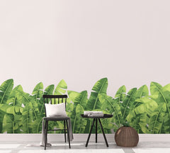 Wall with large banana wall stickers, wooden chair sitting in front.
