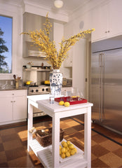 White kitchen, focus of the photo is a white mobile island in the middle of the kitchen with a vase of flowers and glasses sitting on top.