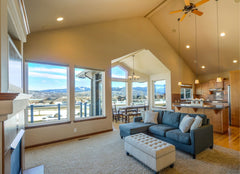 Large open floor plan living room and kitchen with a ceiling fan