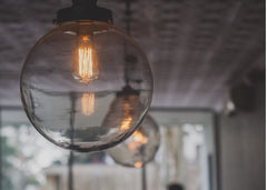 Close up of a round clear semi-flush mount light fixture with an Edison bulb.