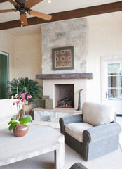 Neutral living room with a fireplace in the background, wooden ceiling fan