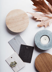 White background, some laminate samples in gray and black, a wood sample, and a leaf as well as a round concrete candle holder with a candle in it.
