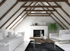 Simple living room set within an attic space with sharp angled roof and wooden beams.  All of the furniture is white, except for the rug which is black.