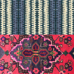 2 different rugs, top rug is blue and white striped, bottom rug is pink with a medallion
