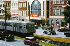 Close up of a model train set up in cityscape.