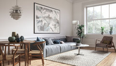 Modern space, with a gray couch, simple design, large artwork on wall.