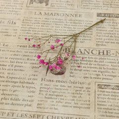 Beige newsprint wallpaper with a sprigg of a pink flower sitting on it.