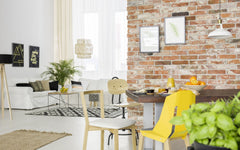 Open loft space with a brick wall, focus is on dining room table, but you can look past it to the living room.  Multiple rugs are on the floor.