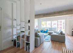 Open shelving with books on it helping to divide up a large living room space.