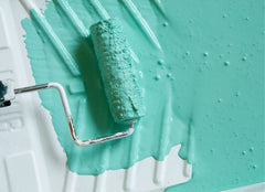 Closeup of paint pan with seafoam green paint and a paint roller.
