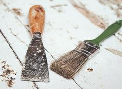 Paint scraper next to a clean paint brush on a white wooden floor
