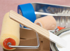 Close up of various painting supplies: paint pan, roller, brushes, tape, can of open paint with a mixer in it.