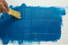 Someone using a brush to paint blue paint over a white wall tile.