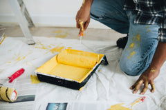 Man bending down to get yellow paint on a roller to paint a wall.