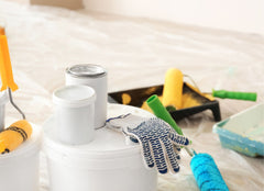 Close up of painter's tools - gloves, paint cans, drop cloths, roller brushes