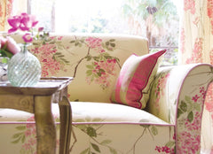 Sofa with a floral pattern in pink, coffee table sitting in front with a crystal vase.
