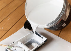 A large bucket of primer being poured into a pan.