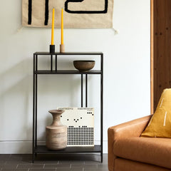 Thin metal entry table with various items sitting on it.